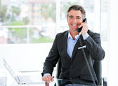 Confident mature businessman talking on phone — Stock Photo