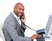 Smiling Afro-American businessman talking on phone — Stock Photo