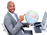 Smiling businessman holding a terrestrial globe — Stock Photo
