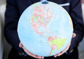 Close-up of a business person holding a terrestrial globe — Stock Photo