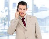 Assertive businessman talking on phone standing — Stock Photo