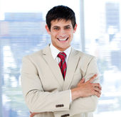 Smiling businessman with folded arms standing — Stock Photo