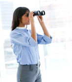 Confident female executive looking through binoculars — Stock Photo