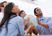 International business team holding a terrestrial globe — Stock Photo