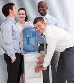 Confident multi-ethnic business interacting at a watercoo — Stock Photo