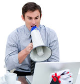Angry businessman yelling through a megaphone sitting at his des — Stock Photo