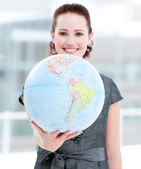Assertive businesswoman holding a terrestrial globe — Stock Photo