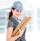 Portrait of a smiling female architect holding blueprints — Stock Photo