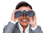 Assertive businesswoman looking through binoculars — Stock Photo