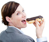 Glowing businesswoman eating a chocolate eclair — Stock Photo
