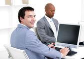 Glada unga affärsmän som arbetar på datorer — Stockfoto
