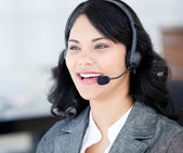 Joyful businesswoman wearing a headset to talk with customer — Stock Photo