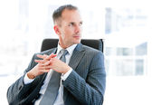 Confident businessman thinking about the company — Stock Photo