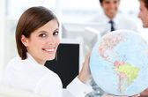 Smilling businesswoman holding a globe — Stock Photo