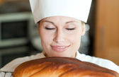 Radiant female chef baking bread — Stock Photo