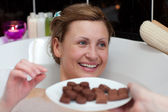 Bright woman eating chocolate while having a bath — Stock Photo