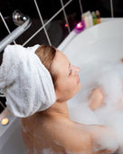 Caucasian woman taking in a bubble bath — Stock Photo