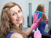 Charming woman cleaning a bathroom's mirror — Stock Photo