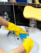 Close-up of a woman cleaning a bathroom's sink — Stock Photo