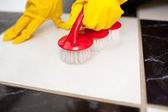 A person cleaning a bathroom's floor with a yellow rubber glove — Stock Photo