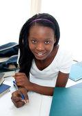 Niña adolescente sonriente estudiar acostado en su cama — Foto de Stock