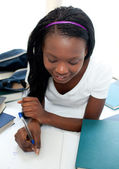 Affascinante ragazza adolescente studiando sdraiato sul suo letto — Foto Stock