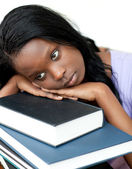 Annoyed student leaning on a stack of books — Stock Photo