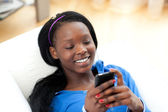 Radiant woman sending a text lying on a sofa — Stock Photo