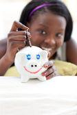 Cheerful teen girl putting money in a piggy-bank — Stock Photo