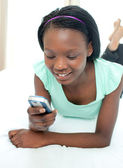 Cute teen girl using a mobile phone lying on her bed — Stock Photo