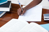 Close-up of an Afro-American girl doing her homework — Stock Photo