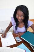 Gülümseyen afro-amerikan teen kız ödevini yapıyor — Stok fotoğraf