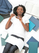 Serious student doing her homework lying on a bed — Stock Photo