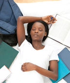 Tired student doing her homework lying on a bed — Stockfoto