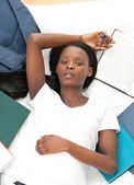 Young student doing her homework lying on a bed — Stock Photo