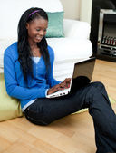Afro-american woman using a laptop sitting on the floor — Stock Photo