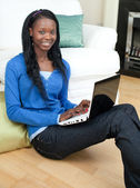 Charming woman using a laptop sitting on the floor — Stock Photo
