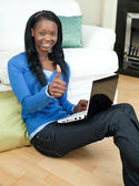 Happy woman using a laptop sitting on the floor — Stock Photo