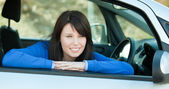 Charming teen girl smiling at the camera sitting in her car — Stock Photo
