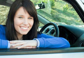Happy teen girl smiling at the camera sitting in her car — Stock Photo