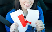 Charming teen girl sitting in her car tearing a L-sign — Stock Photo