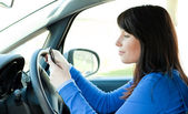 Attractive teen girl using a mobile phone while driving — Stock Photo