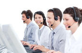 Multi-cultural customer service agents working in a call center — Stock Photo
