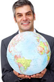 Mature businessman holding a terrestrial globe — Stock Photo