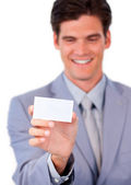 Charming businessman holding a white card — Stock Photo
