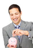 Attractive businessman saving money in a piggy-bank — Stock Photo