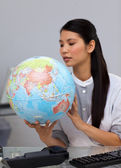 Concentrated businesswoman looking at a globe — Stock Photo