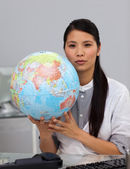 Charming asian businesswoman holding a globe — Stock Photo