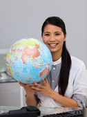 Assertive asian businesswoman holding a globe — Stock Photo