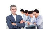 成熟したマネージャーと彼のチームの会議でメモを書く — ストック写真